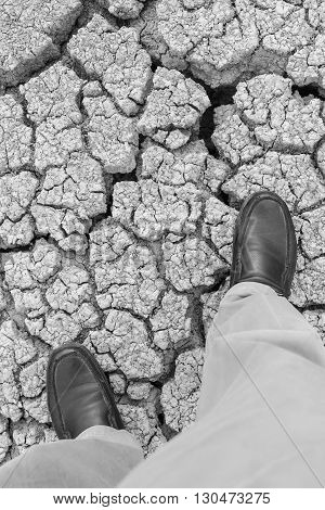 business man step on crack earth in black and white tone