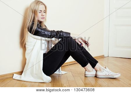 young pretty teenage blond girl sitting on floor at home despair sad alone, lifestyle concept in white interior