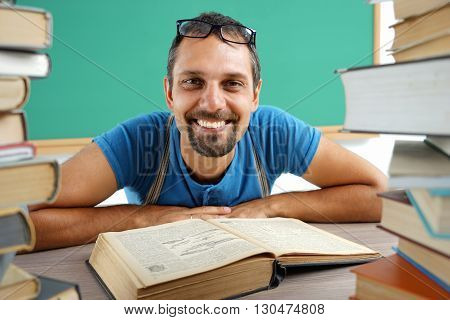 Happy joyful student reading a book. Photo of man wearing glasses creative concept with Back to school theme