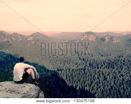 Moment Of Loneliness. Man In Shirt Sit On The Cliff Of Rock And Watching Into Forest Valley.
