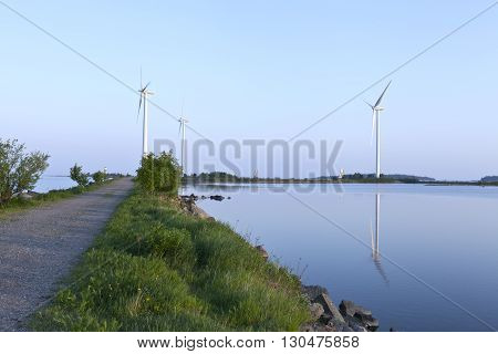 UMEA, SWEDEN ON JUNE 02. View of a wind power park, pylons and a lighthouse on June 02, 2013 in Holmsund, Sweden. Path, gravel road up to the windmills. Summer evening. Editorial use.