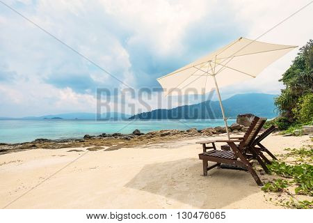 Beach chairs with parasol on the beach in the island in cloudy day