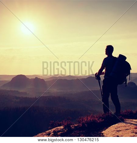 Tall Backpacker With Poles In Hand. Sunny Daybreak In Mountains. Hiker With Big Backpack On Rocky Vi