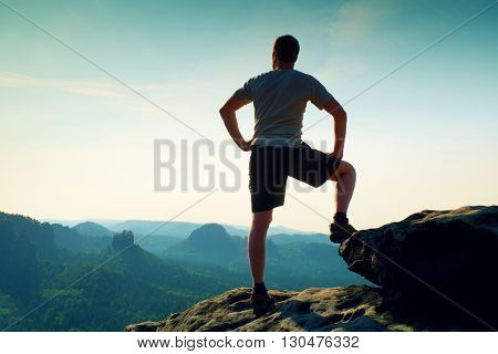Sportsman In Shirt And Pants. Man Is Standing On The Peak Of Sandstone Cliff In Rock Empires Park An