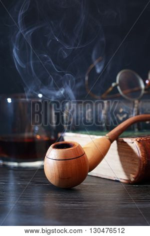 Wooden smoking pipe on old book near glass of alcohol