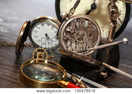 Clock workshop. Vintage still life with ancient silver pocket watch
