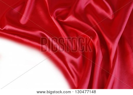Closeup of folds in red silk fabric on plain background.