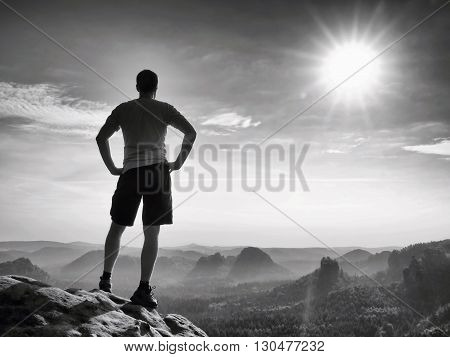 Happy Hiker Is Standing On Sharp Cliff  In Rock Empires Park And Watching Over The Misty And Foggy M
