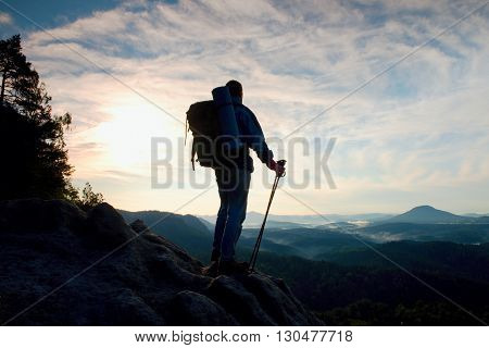 Tourist With Big Backpack And Poles In Hands Stand On Rocky View Point And Watch Into Deep Misty Val