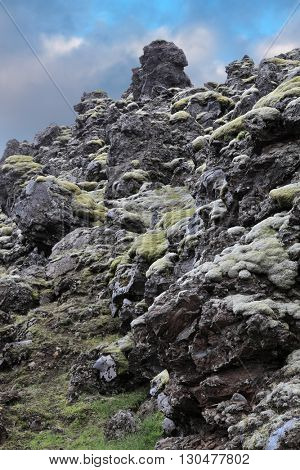National Park Landmannalaugar in Iceland. Pieces of gray and black lava, sometimes covered with green moss.