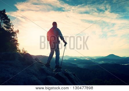 Tourist Guide With Pole In Hand. Hiker With Sporty Backpack Stand On Rocky View Point Above Misty Va