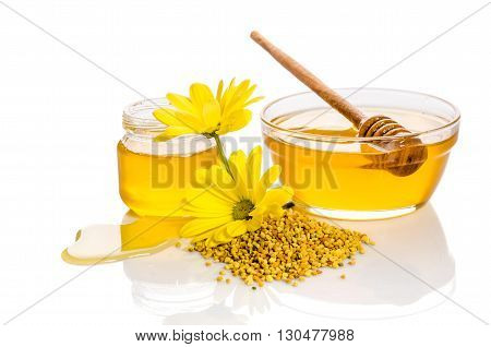 the bowl and the jar of honey near a pile of pollen and flower isolated on white