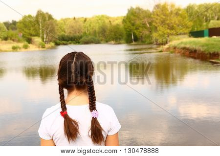 teen girl with plait back close up portrait on the summer lake nature background