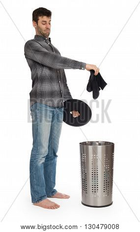 Young Man Putting A Dirty Socks In A Laundry Basket