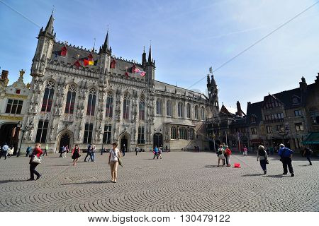 Bruges Belgium - May 11 2015: Tourist on Burg square with City Hall in Bruges Belgium on May 11 2015. The historic city centre is a prominent World Heritage Site of UNESCO.