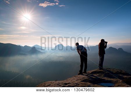 Two Friends. Hiker Thinking And Photo Enthusiast Takes Photos  Stay On Cliff. Dreamy Fogy Landscape,