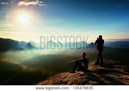Hiker And Photo Enthusiast Stay With Tripod On Cliff And Thinking. Dreamy Fogy Landscape, Blue Misty