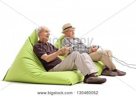 Two seniors sitting on green beanbags and playing video games isolated on white background