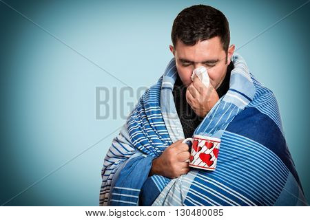 Portrait of a sick man with the flu, allergy, germs,cold, blowing his nose with tissue and holding a warm tea cup