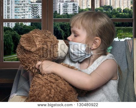 Little girl in medical mask kissing toy bear. House, windows buildings, city, green trees, summer. Conceptually about diseases, infections and allergies
