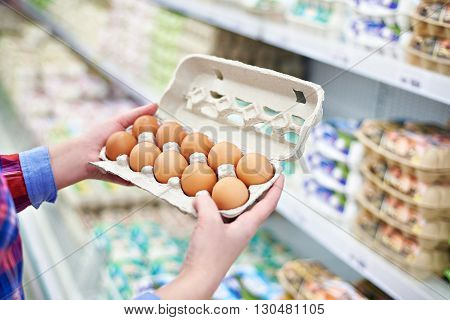 In Hands Of Woman Packing Eggs In Supermarket