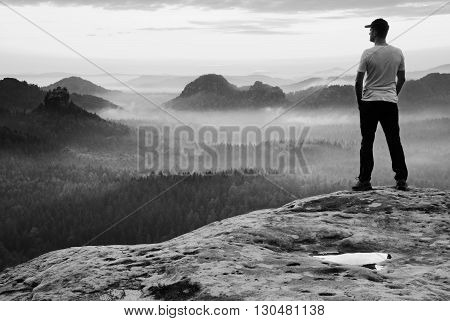Tall Man In White Shirt And  Black Trousers With Red Baseball Cap  Stay On Sharp Cliff And Watch To