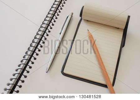 A small note pad on a larger spiral bound sketch pad with a silver cased pen and a plain lead pencil.