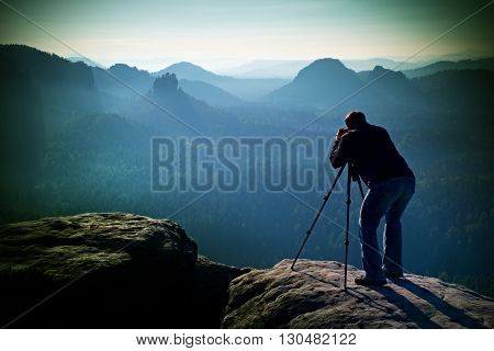 Professional On Cliff. Nature Photographer Takes Photos With Mirror Camera On Peak Of Rock. Dreamy B