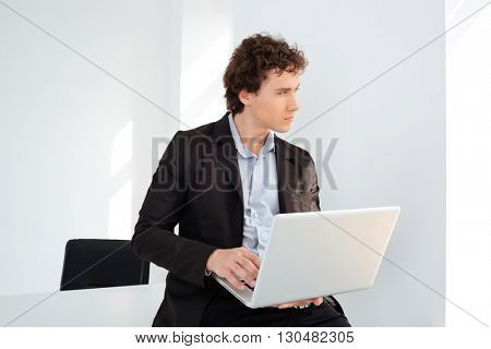 Pensive businessman leaning on the table with laptop computer and looking away