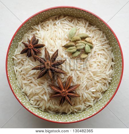 Uncooked long grain basmati rice in a colorful ceramic bowl with star anise and cardamom pods.