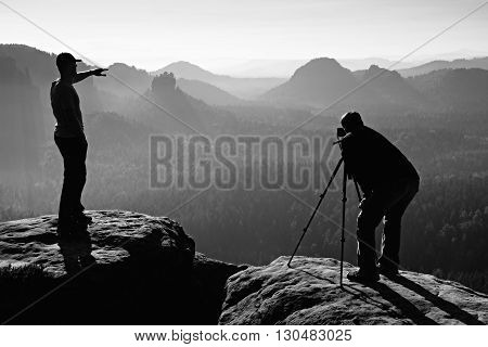 Tourist Guide And Photo Enthusiast Stay With Tripod On Cliff And Thinking. Dreamy Fogy Landscape, Bl