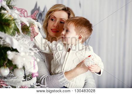 Mother with her Little son decorating christmas tree with toys and flowers. Family preparing home for xmas celebration.