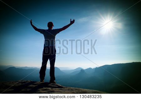 Happy man gesture of triumph with hands in the air. Funny hiker on the peak of sandstone rock in national park Saxony Switzerland