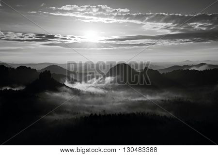 Autumn misty daybreak. Misty awakening in a beautiful hills. Peaks of hills are sticking out from foggy background