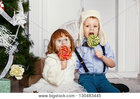 Little Children Eating A Lollipops.