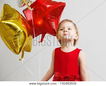 Little Baby Girl With Colorful Shiny Foil Balloons