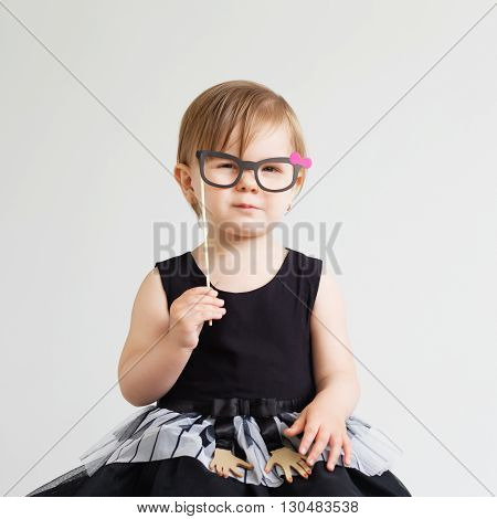 Portrait Of A Lovely Little Girl With Funny Photo Props Paper Glasses Against A White Background