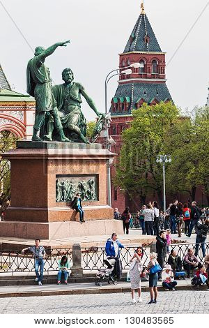 Moscow Russia - May 2 2016: Tourists and citizens walking in the Moscow Kremlin. Monument to Minin and Pozharsky in St. Basil's Cathedral of Kremlin fortress Russia.