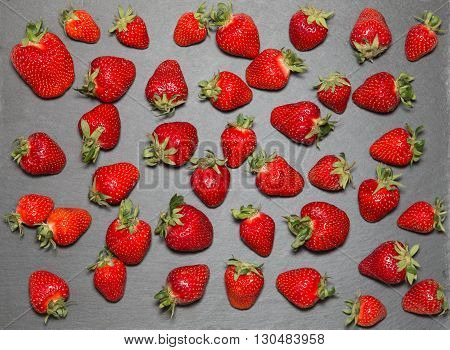 Strawberry raw fruit on gray slate tray organic fresh produce