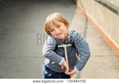 Close up portrait of adorable young 4 years old blond boy leaning on his scooter