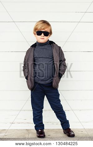 Fashion kid in sun glasses, cute little boy wearing dark jacket, trousers, roll neck t-shirt and moccasins, standing against white wooden background