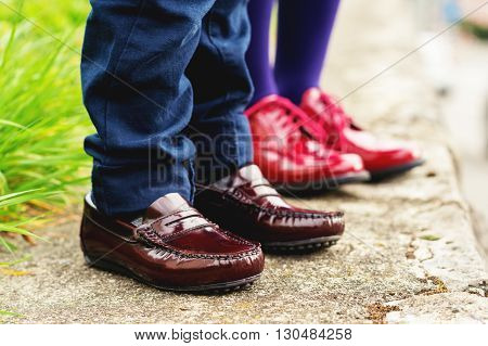 Two pairs of kids feet wearing fashion shoes