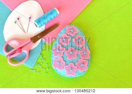 Felt Easter egg with flowers. Scissors, thread, needle, pins, paper templates. Macro.