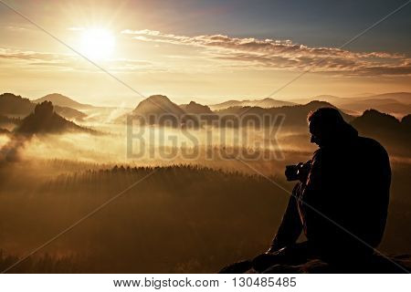Happy Tourist With Camera In Hands Sit On Peak Of Sandstone Rock And Watching Into Colorful Mist And