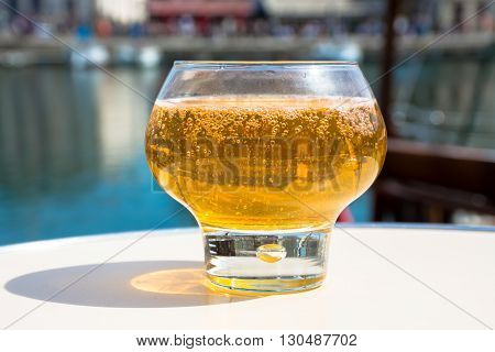 Normandy apple cider in traditional glass in old French fisherman village
