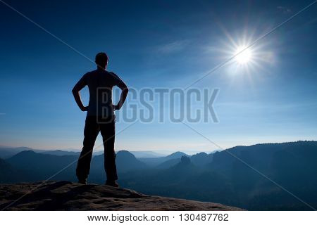 Slim tourist on sharp peak of rock watch over misty and foggy morning valley to Sun. Dreamy morning nature