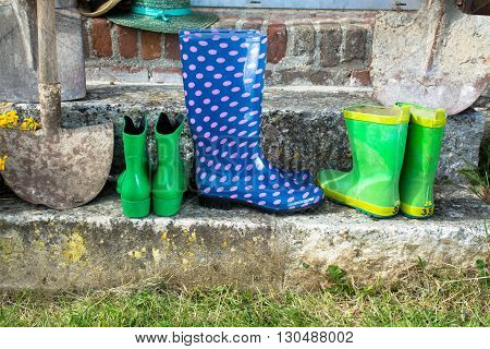Garden equipment - rubber boots schovels and srtaw hats in sunny day on old stone wall background