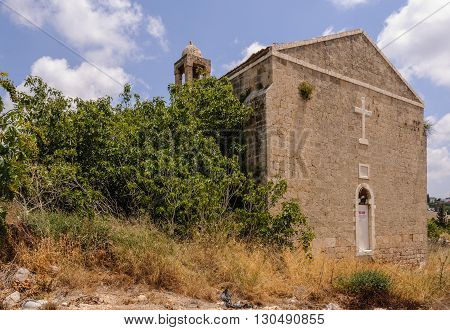 Abandoned church:   The church of the abandoned village Ba'sa in the Galilee, Israel, is still standing since 1948. Wild growing tree looks like grows out of the church wall.