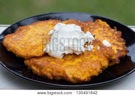 Potato and carrot pancakes with sour cream close up