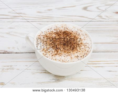 Cup of cappuccino with cinnamon on white wooden background
